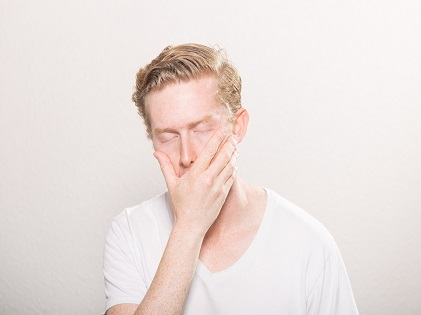 man sleepy covering mouth face
